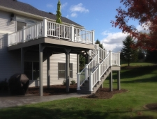 Light grey second story deck with stairs and white banister