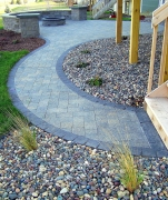 Grey-blue stone patio with wall, fire pit and curved walkway
