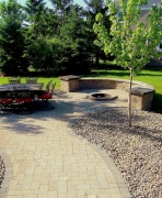 Semi-circle stone bench around in-ground fire pit