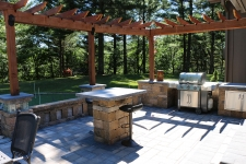 Backyard kitchen with stone floor and wood pergola