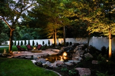 Backyard with rock water feature with water light and patio