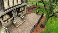 Fenced in cobblestone patio and stone stairs to house