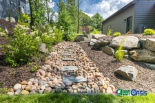 rock creek bed and softscaping on side of house