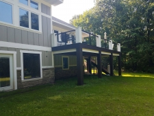 Dark brown second story deck with thick beams and white accents