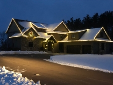 Snow-covered roof with yellow bulb lights around perimeter