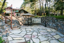 In-ground patio with various piled up rocks retaining wall