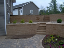 Dual level tan brick retaining wall with rock garden