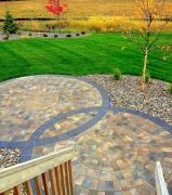 Overlapping radial brick pattern patio surrounded by loose rocks