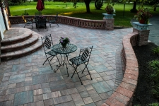 Circular patio with rectangle stones and short brick wall