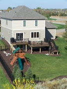 Light brown second story deck with stairs and black railing