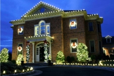 Brick house trimmed with yellow lights and wreaths in windows