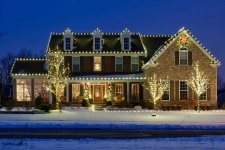 Brick house with lights around roof and front yard trees