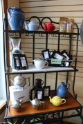 Black shelf with tea flavors and colored kettles displayed