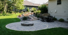 Grey-blue radial pattern backyard patio with raised fire pit