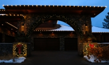 Brick archway of house leading into garage with lit up wreaths