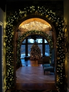 Arched interior doorway of house outlined in lit wreath
