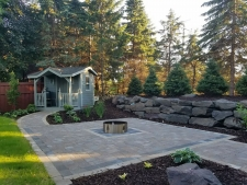Square stone patio surrounded by wood chips and retaining wall