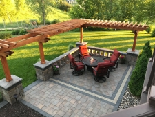 Square stone patio with tabletop fire pit and pergola
