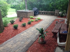 Brick patio with walkway surrounded by red cedar wood chips