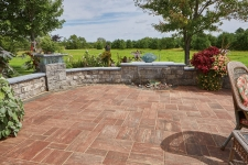 Light reddish-brown stone patio with retaining wall