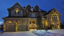 Snowy front yard of house trimmed with wreaths and lights