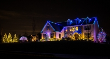 Roof trimmed with blue lights and trees with colored lights