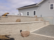 Retaining wall with stairway on side of house