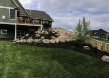 Retaining wall made from dark wood chips and boulders
