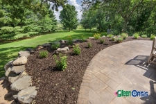 chocolate mulch and plants near retaining wall and patio