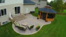 Organic shaped tan and grey brick backyard patio with gazebo