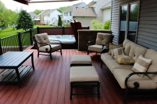 Brownish-red wood deck with surrounding black metal banister