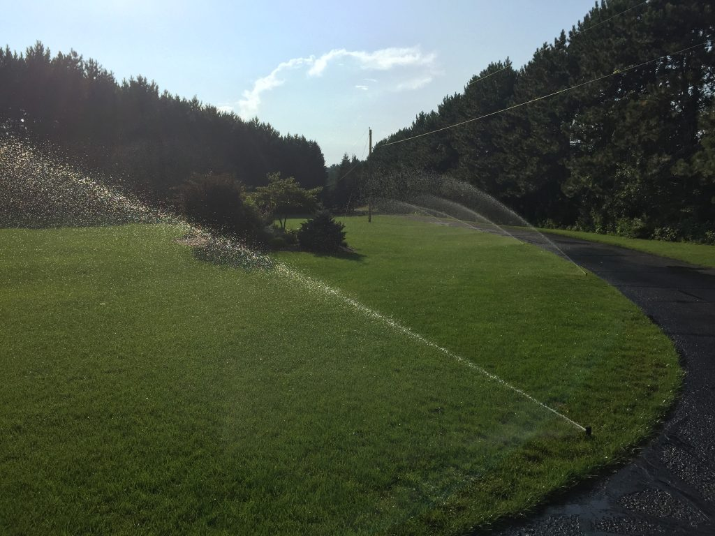 Paved road next to grass with sprinkler system