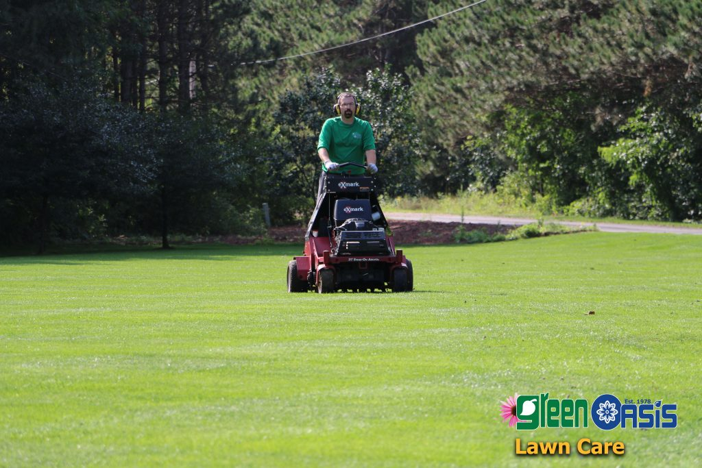Green Oasis worker riding lawnmower